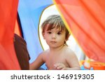 Cute baby having happy playful time in colorful tent on beach - stock photo