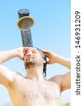 Good looking and attractive man with muscular wet body taking bath shower on resort pool outdoors - stock photo