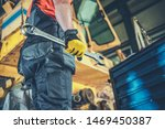 Caucasian Men with Large Iron Wrench Fixing Heavy Machinery. Industrial Job. - stock photo