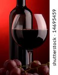 a glass of red wine grape and bottle - stock photo
