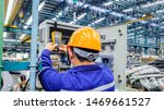 Small photo of Blur background of electrical engineer are working on factory site, Technician check fault in power control unit on factory site, Electrician are checking fault in control box