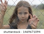 Small photo of A girl looks at the world through a metal mesh. Infringement of the rights of the child