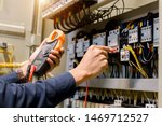 Electrician engineer work  tester measuring  voltage and current of power electric line in electical cabinet control. - stock photo