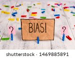 Small photo of Conceptual hand writing showing Bias. Business photo text inclination or prejudice for or against one demonstrating group Crumbling sheet with paper clips placed on the wooden table.