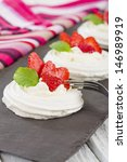 Strawberry Meringue Nests - Meringue discs topped with whipped cream and juicy strawberries.  - stock photo
