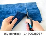 Small photo of Woman hand holding a scissors and cutting out a folded in half blue jean shorts. Shorten the denim shorts with scissors and sewing pin. Shorten the jeans. DIY shorts out of jeans.