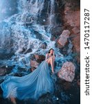 Small photo of lost princess sitting on wet stones near gorgeous high waterfall, lady in blue dress with delightful long amazing train laid out on water, picked up legs and thought, fairy-tale daughter of aqua
