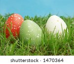 Three speckled eggs in grass - stock photo