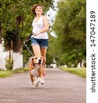 Stock photo happy young woman jogging with her beagle dog 147047189