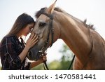 Tenderness, love and animals concept. Sensual young woman touching horses foretop, close eyes and gently brushing nose as taking care pet, adore spending time horse farm, horsewoman on rancho