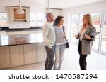 Small photo of Female Realtor Showing Couple Interested In Buying Around House