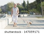 Stock photo senior woman walking her dog 147059171