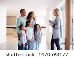 Small photo of Female Realtor Showing Family Interested In Buying Around House