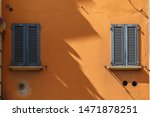 Small photo of Two windows with wooden shutters on an orange house: one sunlit, the other in shadow, divided by a jagged line. Long shadows. In Bologna, Italy. Splitting concept.