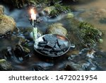 Stock photo norse runes in a forged bowl with candle in the evening on the river 1472021954