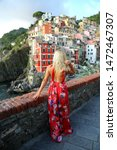 Small photo of Blond girl traveller in a long red dress enjoying the view of Cinque Terra Liguria Italy. Freedom concept. Luxury lifestyle.