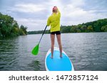 a woman stands on a sup board... | Shutterstock . vector #1472857124