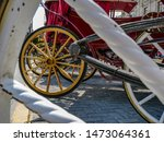 Small photo of View of red, romantic horse carriages through he spokes of a white, wooden carriage wheel