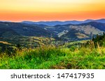 high meadow with views of the mountain panorama in the early morning - stock photo