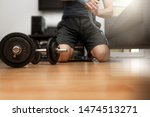 Fitness concept. Dumbbell on the floor. Man starting strenght and boxing training at home. Athlete putting wraps on hand. Motivation to act. Determination, challenge.  - stock photo