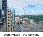 Rain drops on window glass pane, cityscape background. London Ontario Canada