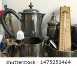 A collection of pewter jugs and tableware with a thermometer.