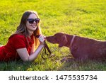 Stock photo girl in red clothing and sunglasses playing with the dog in the green grass on a sunny lawn 1475535734