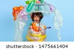 Small photo of Shocked female with Afro hairstyle stands under polythene umbrella, wrapped in cellophane, gazes with great wonder at plastic garbage, tired after collecting waste, brings litter for recycling