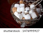 Small photo of London UK July 2019: Vintage silver plated sugar tongs and sugar cubes in a crystal dish on a dark wooden table.