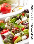 Refreshing crispy Greek salad with cherry tomatoes, olives, bell pepper, caperberries, and feta cheese.  - stock photo