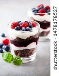 Small photo of Layered trifle dessert with chocolate sponge cake, whipped cream, berries and fruit jelly in serving glasses.