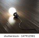 Glowing light bulb with black wire on wooden table. - stock photo