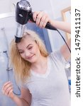 Small photo of Haircare. Beautiful long haired blonde woman drying hair in bathroom. Smiling girl blowing wind on wet head using holding hairdryer in hand.