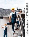 Small photo of selective focus of workman standing on ladder with toolbox near coworker