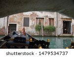 Small photo of Venice winter mysterious romantic: Gondola sailing with parsimony between the canals, crossing under bridges