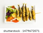 Stock photo fried horse mackerel istavrit fish skewered wooden sticks on the white color long plate with 1479672071