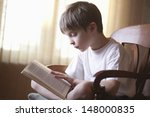 Young Boy Reading Book On Chai...