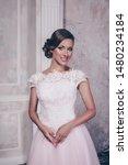 Small photo of Beautiful pink wedding dress. Bride in wedding dress. Wedding dress in Paris. Bride in a luxury apartment in a wedding dress.