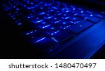 Small photo of A laptop keyboard with blue light at night. Enter button focused. Mostly dark and blue tones. Technological device. Close up shot. Number buttons.