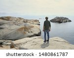 Man standing on a rock and admiring magestic view  of islets and rocks in The End of the Earth in Norway. Verdens Ende (World