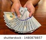 Hands Holding 100 Dollar Bills...