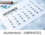 Small photo of Simple 2019 November monthly calendar on table with office supplies