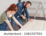 Small photo of Young woman watching her husband doing DIY carpentry during renovations to their home leaning on the planks of wood to steady them as he works