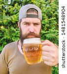 His drinking choice. Hipster drinker. Hipster holding beer mug. Bearded hipster drinking beer on nature. Hipster man with craft beer. Brutal man with drinking habits. Drinking only the best beer.