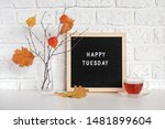Small photo of Happy Tuesday text on black letter board and bouquet of branches with yellow leaves on clothespins in vase on table Template for postcard, greeting card Concept Hello autumn Tuesday.