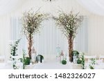 Indoor wedding ceremony with white wedding arch decorated with flowers and big white candles.