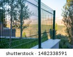 Small photo of Steel grating fence of soccer field,Metal fence wire with bokeh in the background . Coiled razor wire with its sharp steel barbs on top of a wire mesh perimeter fence ensuring safety and security.