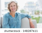 Small photo of Happy woman relaxing on her couch at home in the sitting room