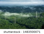 High voltage power transmission towers in fog on mountain mae moh lampang. - stock photo