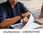 Small photo of Worker checking time and looking at wrist watch at home office. Young Businessman seeing clock to work. On desk with calendar, annual, and summary report.Time out for appointment meeting concept.